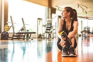 Sport woman relax resting after workout or exercise in fitness gym photo