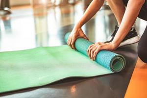 Close up of sporty woman folding yoga mattress in sport fitness photo