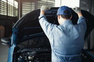Car mechanic opening car hood for internal checking to maintenance photo