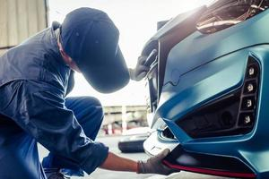 Mecánicos instalando faldón delantero en el garaje del taller de reparación de automóviles foto