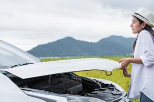 Mujer asiática abriendo el capó del coche para reparar avería coche roto foto