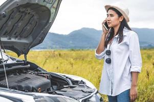 Mujer asiática llamando al servicio mecánico de automóviles para reparar averías foto