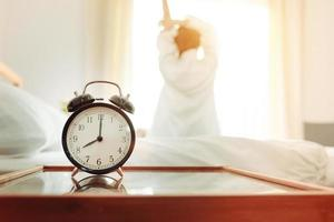 Back view of woman stretching in morning after waking up photo