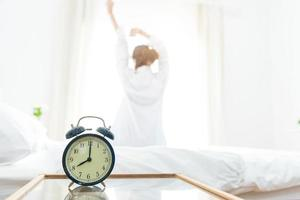 Back view of woman stretching in morning after waking up on bed photo