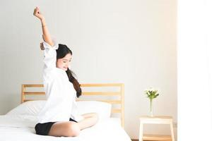 Rear view of woman stretching in morning after waking up photo
