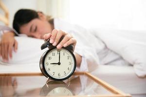 Mujer asiática joven belleza apagar el despertador en la mañana foto