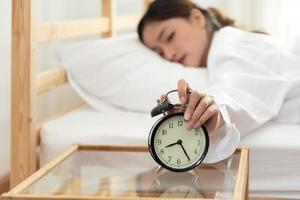 Mujer asiática joven belleza apagar el despertador en la mañana tarde foto