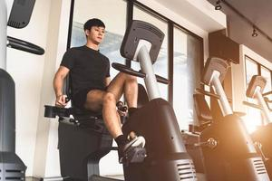 Asian young sport man riding stationary bicycle in fitness gym photo