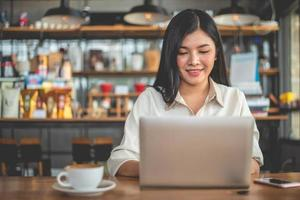 Asian female freelancer smiling when using laptop in cafe photo