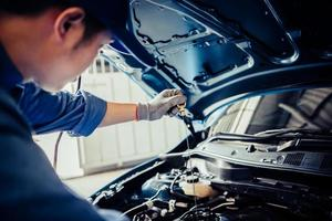 Car mechanic holding checking gear oil to maintenance vehicle photo