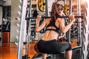 Beautiful sporty sexy woman doing squat workout in fitness gym photo