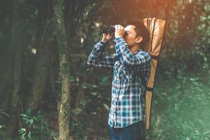 Man with binoculars telescope in forest looking destination photo