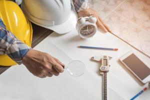 Engineer with magnify glass for looking blank paper for new project photo