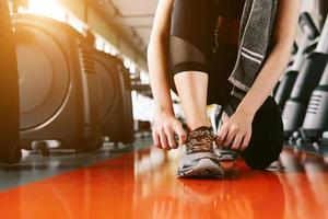 deporte mujer atar la cuerda de las zapatillas de deporte. concepto de centro deportivo y gimnasio foto
