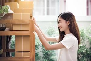 Mujer asiática poner nota adhesiva en papel de paquetería foto