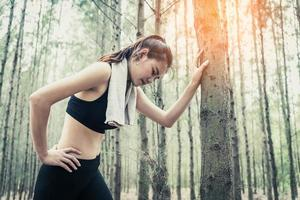 Asian beauty woman tiring from jogging in forest photo
