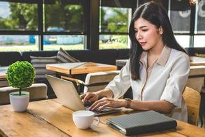 mujer asiática, trabajando, con, computador portatil, en, cafetería foto