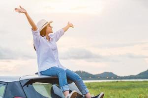 Happy Asian woman spread arms on car roof under sunset photo