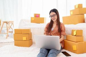 Beauty Asian woman using laptop for customer support in bedroom photo