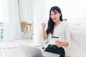 Young Asian woman use credit card for online shopping with laptop photo