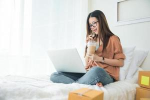 Beauty Asian woman using laptop and drinking coffee on bed photo