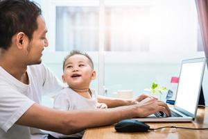 padre soltero e hijo usando laptop juntos felizmente foto