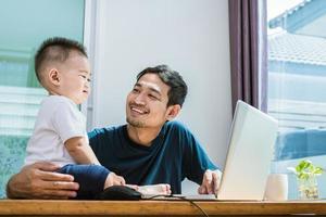 padre e hijo solteros usando laptop juntos. tecnología y estilo de vida foto