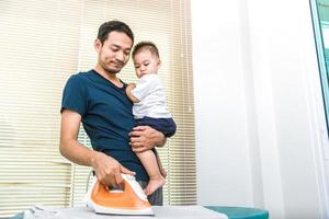 Single dad is ironing while carrying his son. People and Lifestyles photo