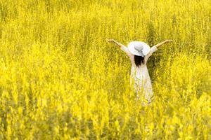 Back view of woman with white wing hat and dress in flower meadow photo