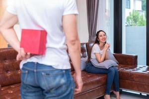chico sorprende a su novia asiática sosteniendo una caja de regalo detrás de él foto