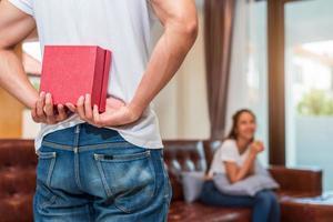 Hombre sujetando un regalo detrás de él para novia sorpresa foto