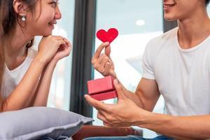 Hombre sujetando caja de regalo para novia sorpresa en su casa foto