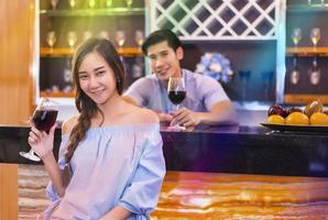 Amantes sonriendo y bebiendo para la luna de miel en el bar. foto
