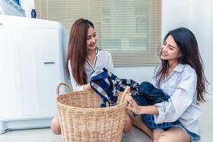 Pareja de mujeres asiáticas haciendo quehaceres domésticos y quehaceres de la lavadora foto