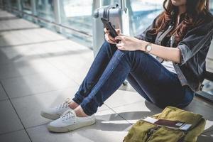 Cerca de la mujer con el bolso y la maleta de equipaje esperando la salida foto