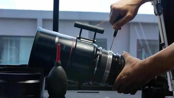 Using a screwdriver to repair a big movie camera  zoom len. video