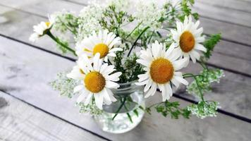 A bouquet of daisies in a glass vase. White daisies in a jar close-up photo