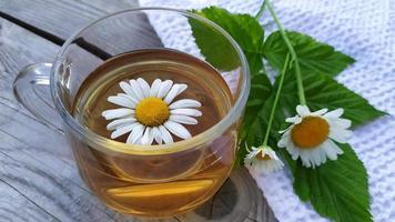 té de manzanilla y flores. taza de té sobre un fondo de madera foto