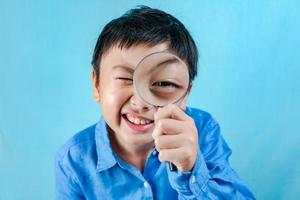 Little boy holding Magnifying glass photo