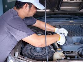 Mechanic holding a block wrench handle while fixing a car. photo