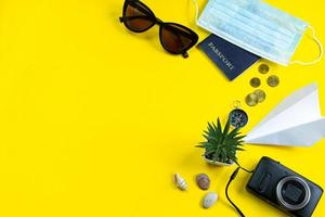 pasaporte, máscara médica y gafas de sol sobre un fondo amarillo. foto