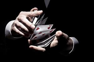 Magician shuffling the cards in a cool way under the spotlight photo