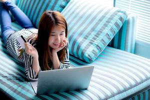 Young asian woman lying using credit card with laptop computer. photo