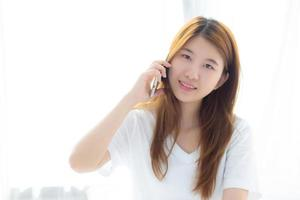 Young asian woman smiling sitting and relax on the bed. photo