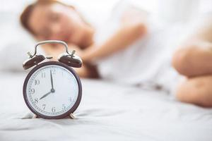 Young asian woman turn off alarm clock in good morning. photo