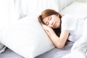 joven asiática dormir acostado en la cama con la cabeza apoyada en la almohada. foto