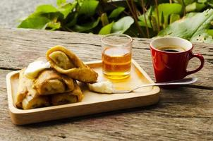 banana french toast with honey on wooden plate and Red coffee cup photo