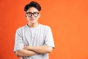 Retrato de hombre asiático sonriente alegre, aislado sobre fondo naranja foto