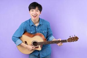 Portrait of Asian man in blue shirt posing on purple background photo