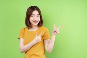 joven asiática posando sobre fondo verde foto